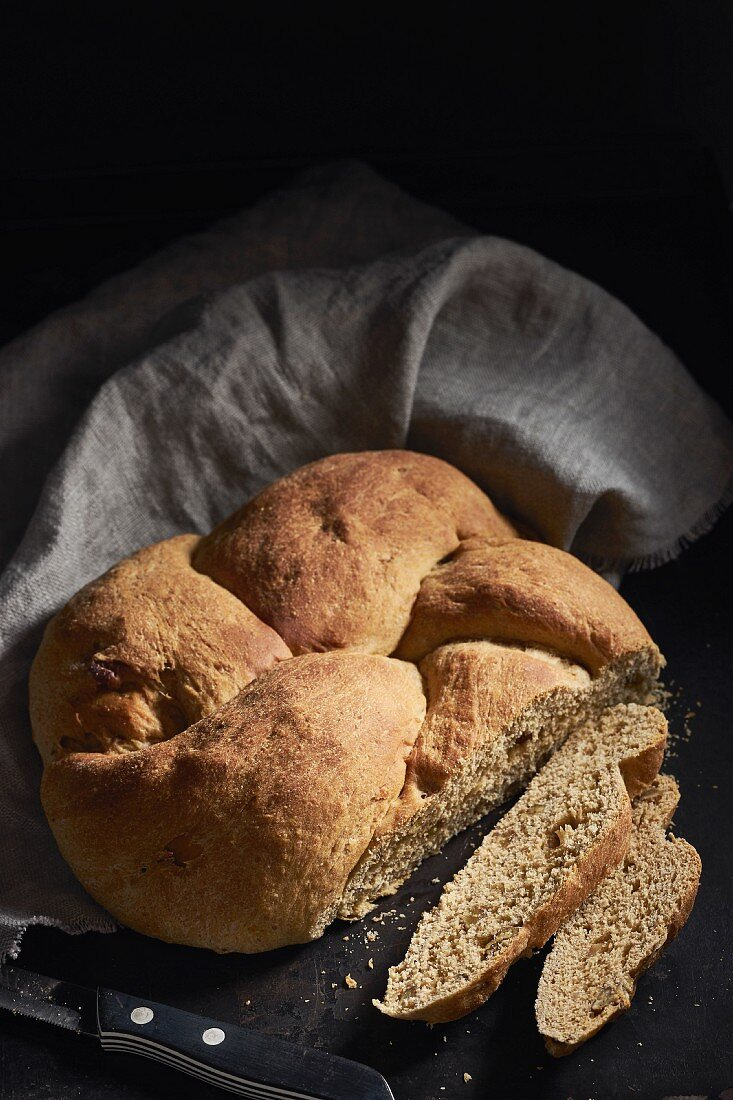 A small loaf of yeast bread with nuts, sliced