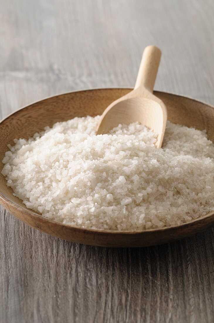 Sea salt in a wooden bowl with a scoop