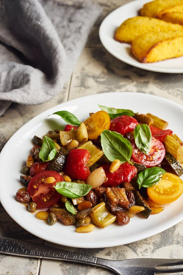 Caponata with peppers and cherry tomatoes served with polenta slices