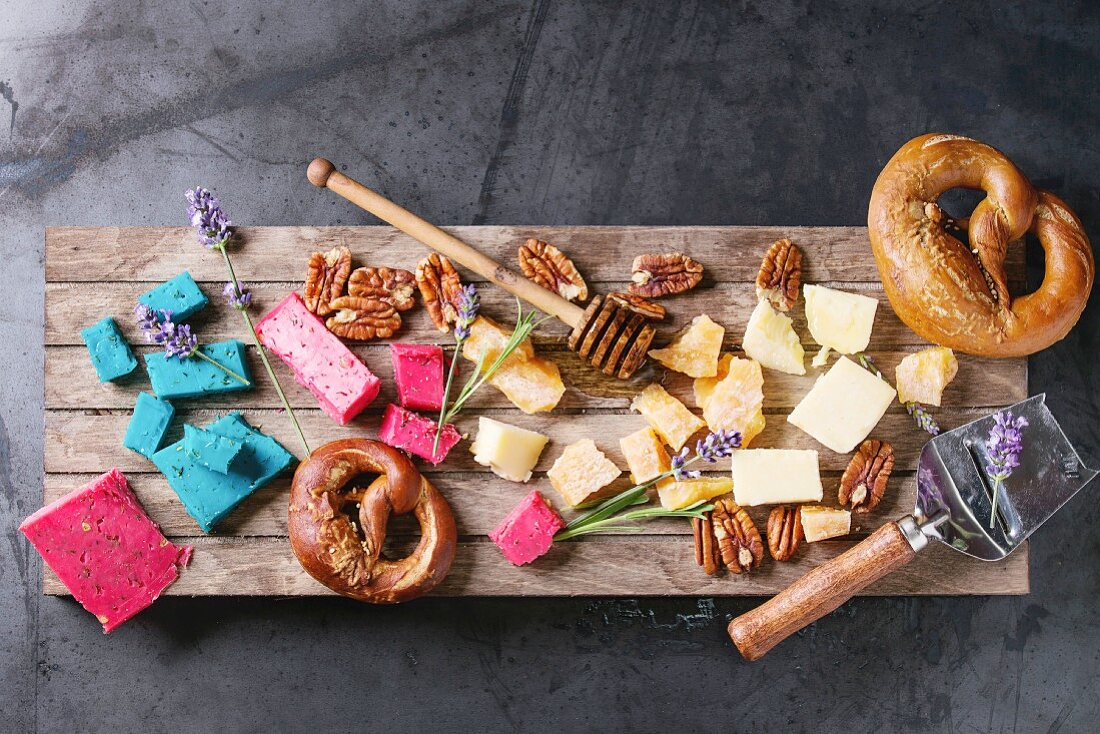 Variety of colorful holland cheese traditional soft, old, pink basil, blue lavender, pecan nuts, honey, lavender flowers, pretzels bread