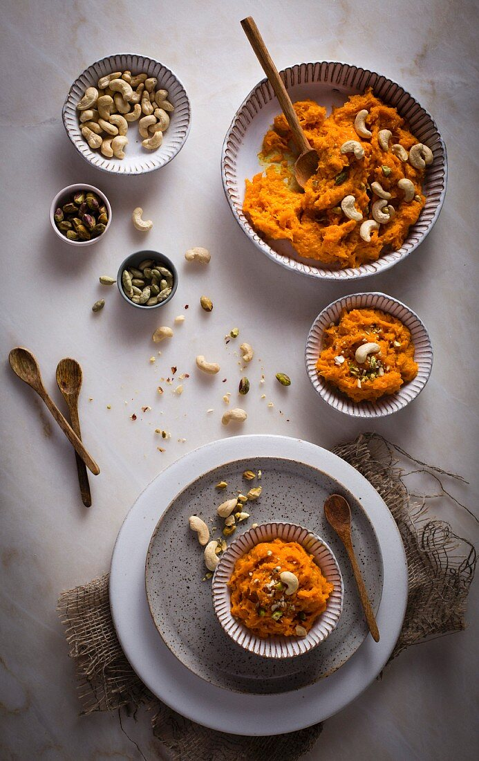 Carrot Halwa (Carrot pudding) with nuts in a ceramic bowl on top view on a marble table