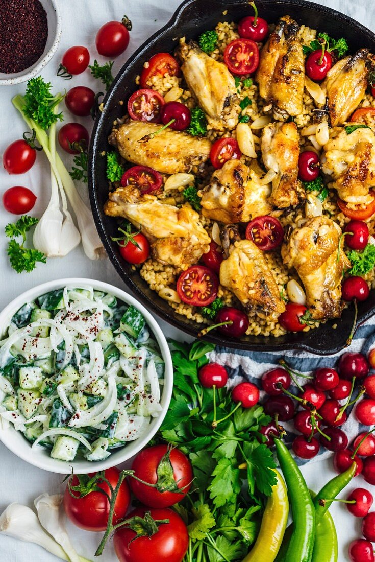 Chicken wings and bulgur pilaf cooked in one pan, garnished with cherries, cherry tomatoes and herbs