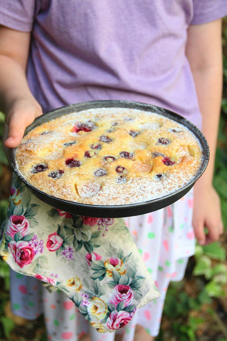 A woman's hand holding a pie dish with apricot and cherry cake