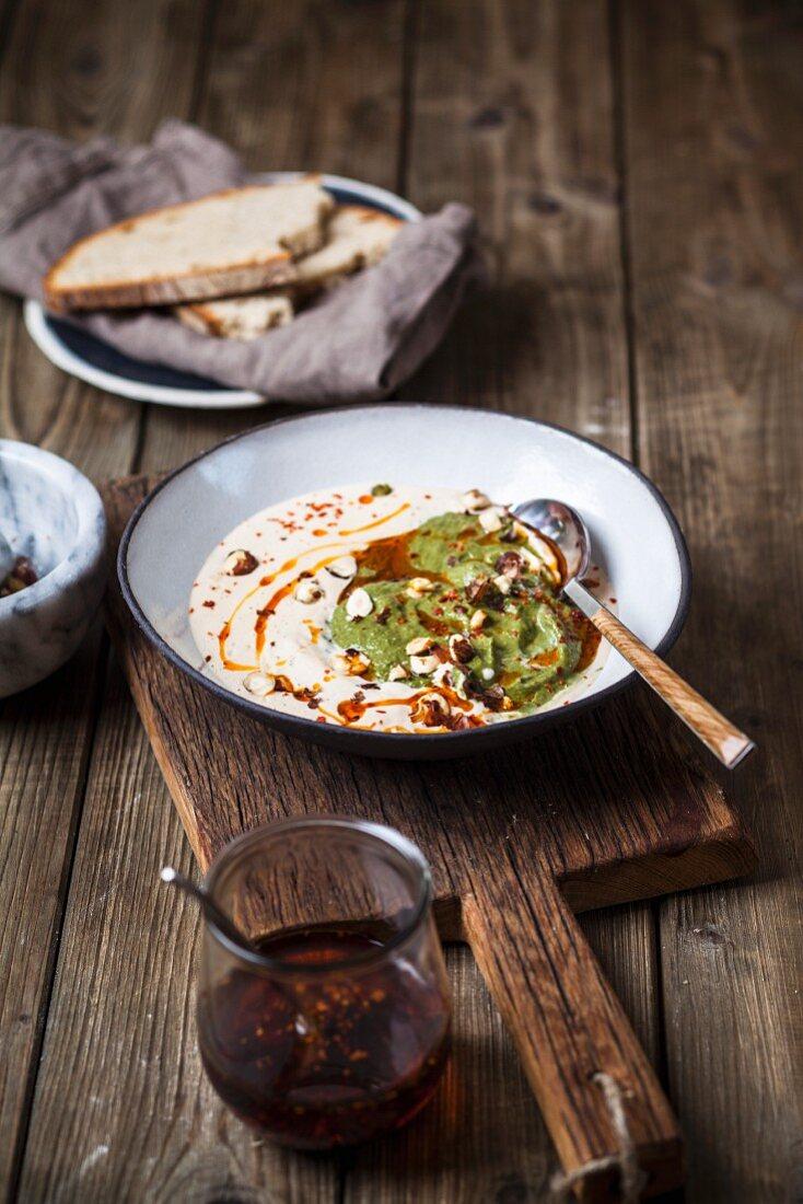 Weiße kalte Knoblauchsuppe mit Haselnüssen, Spinatcreme und Chili-Öl (vegan)