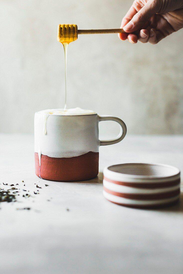 Honig fliesst von Honiglöffel in Keramikbecher mit Tea Latte