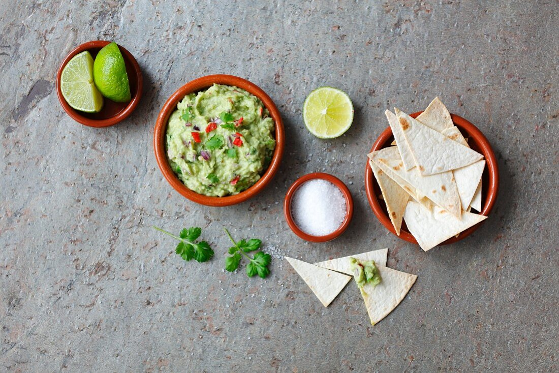 Guacamole, tortilla chips, salt and limes