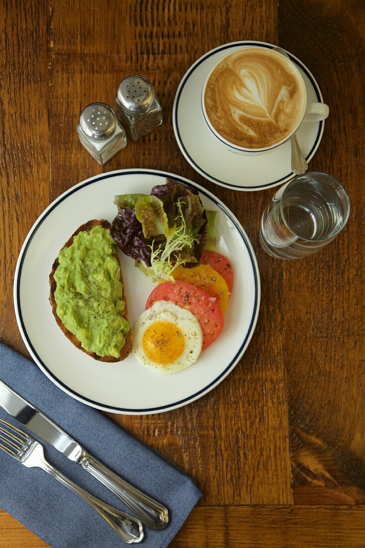 Breakfast with avocado on bread, a fried egg, tomatoes and a cup of coffee
