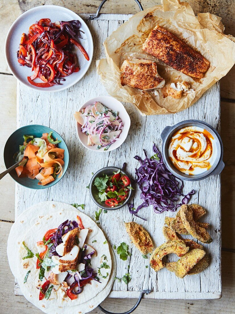 Fish tacos with pickled vegetables, red pepper, coleslaw, yoghurt and avocado