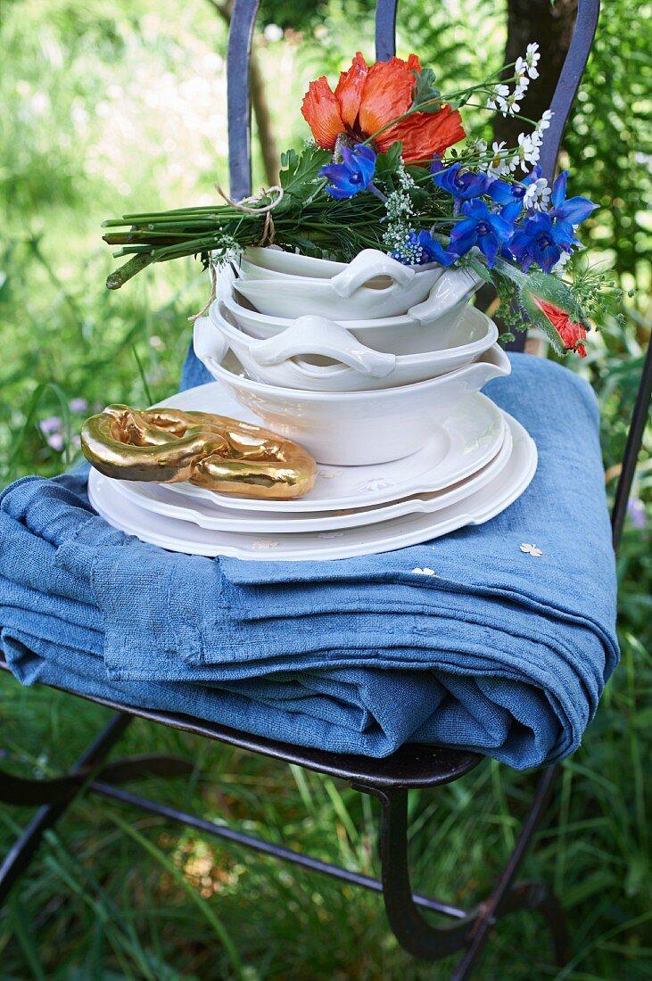 A blue tablecloth, crockery, a bouquet of flowers, and a golden pretzel on a garden chair