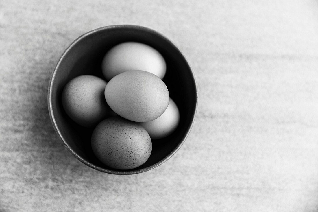A ceramic bowl full of organic free-range eggs (black-and-white photo)