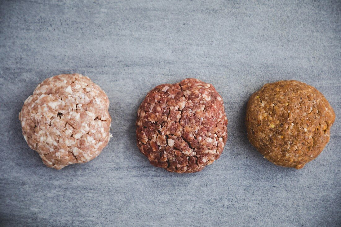 Three different raw organic pork burger patties (seen from above)