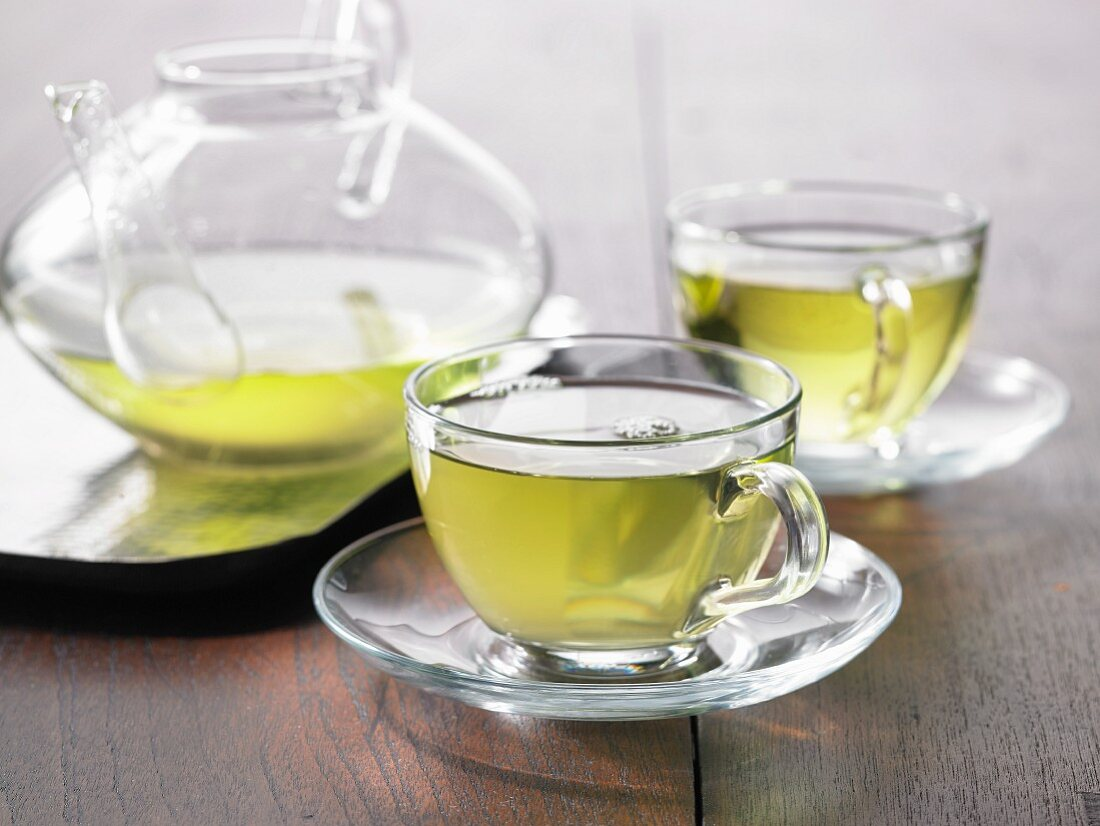 Green tea in a glass cup and a glass pot