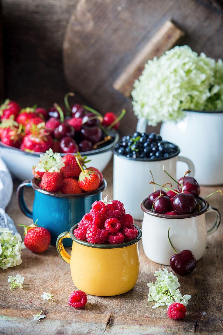 Fresh berries in enamel mugs