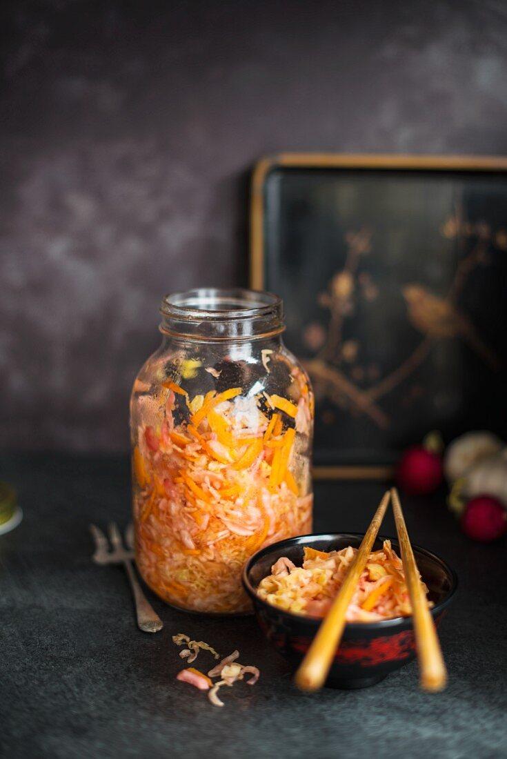 Kimchi (Eingelegter Kohl, Korea) im Glas und in einer Schüssel mit Essstäbchen