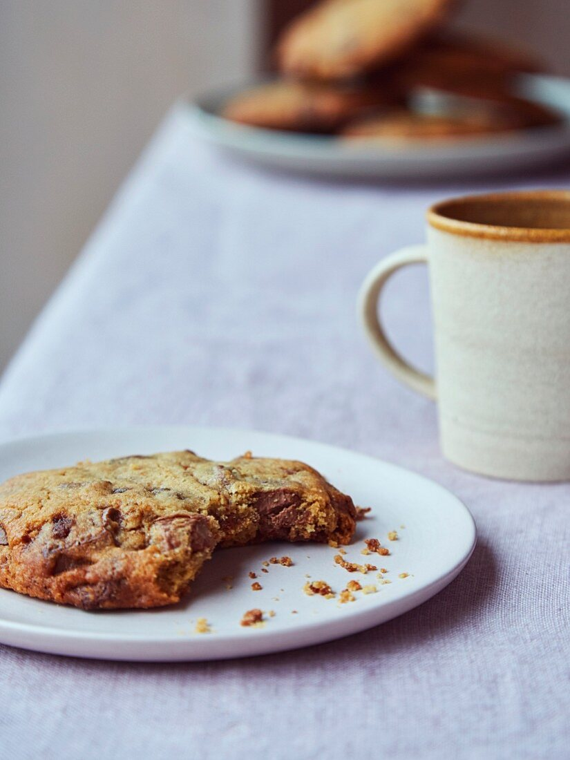 A cup of coffee and a chocolate chip cookie with a bite missing