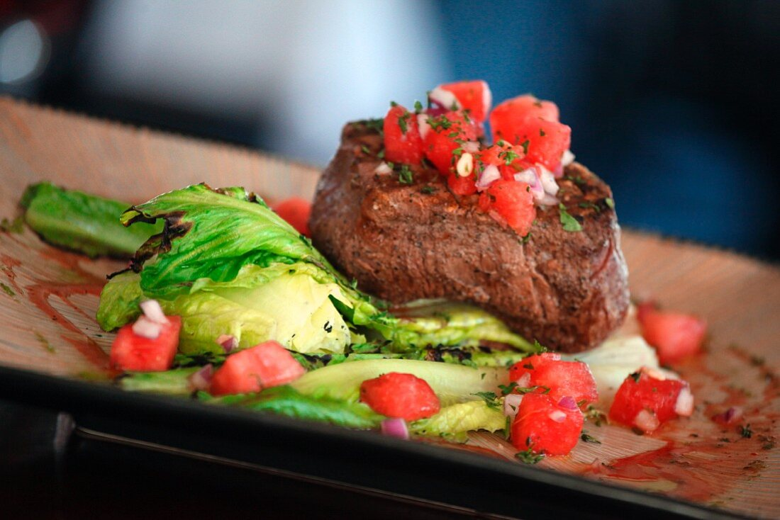 Filet mignon with tomato cubes and salad leaves