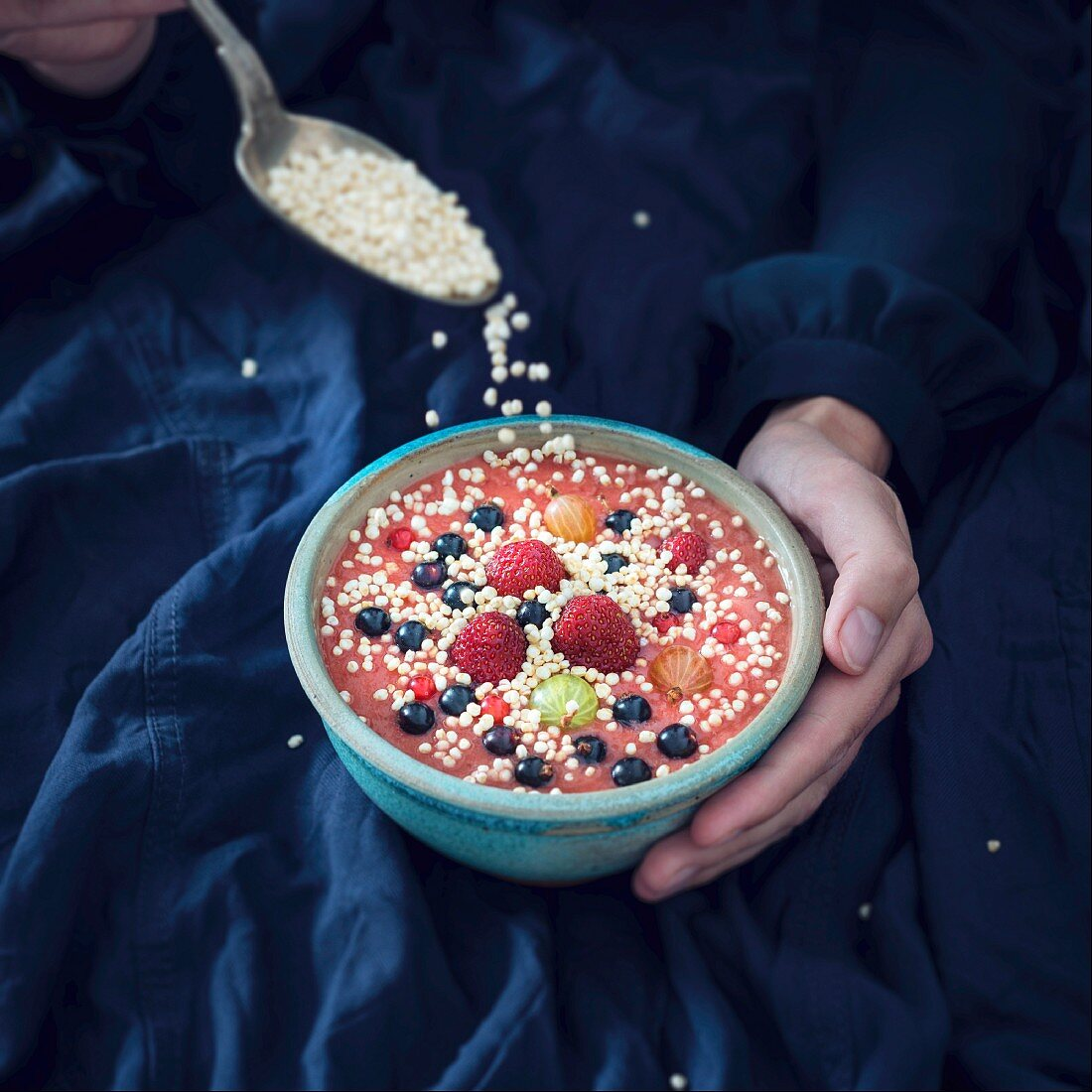 A woman sprinkling quinoa pops over a vegan smoothie bowl with a spoon