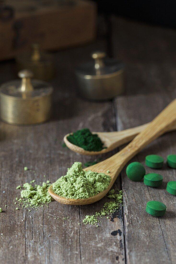 Spirulina tablets and spirulina powder on wooden spoons