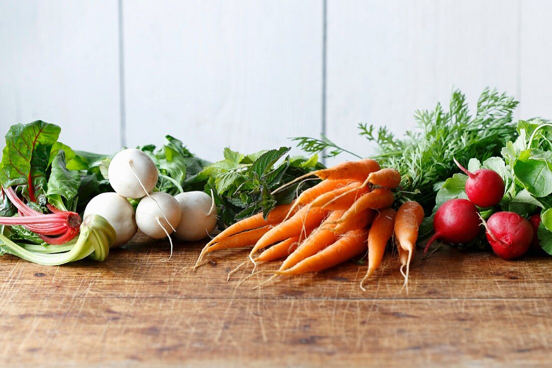 Mangold, turnips, carrots and radishes on a wooden table