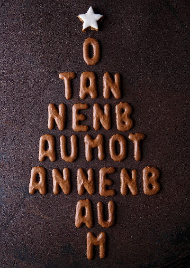 Letter-shaped biscuits arranged in the shape of a Christmas tree, reading 'O Tannenbaum' and topped with a star