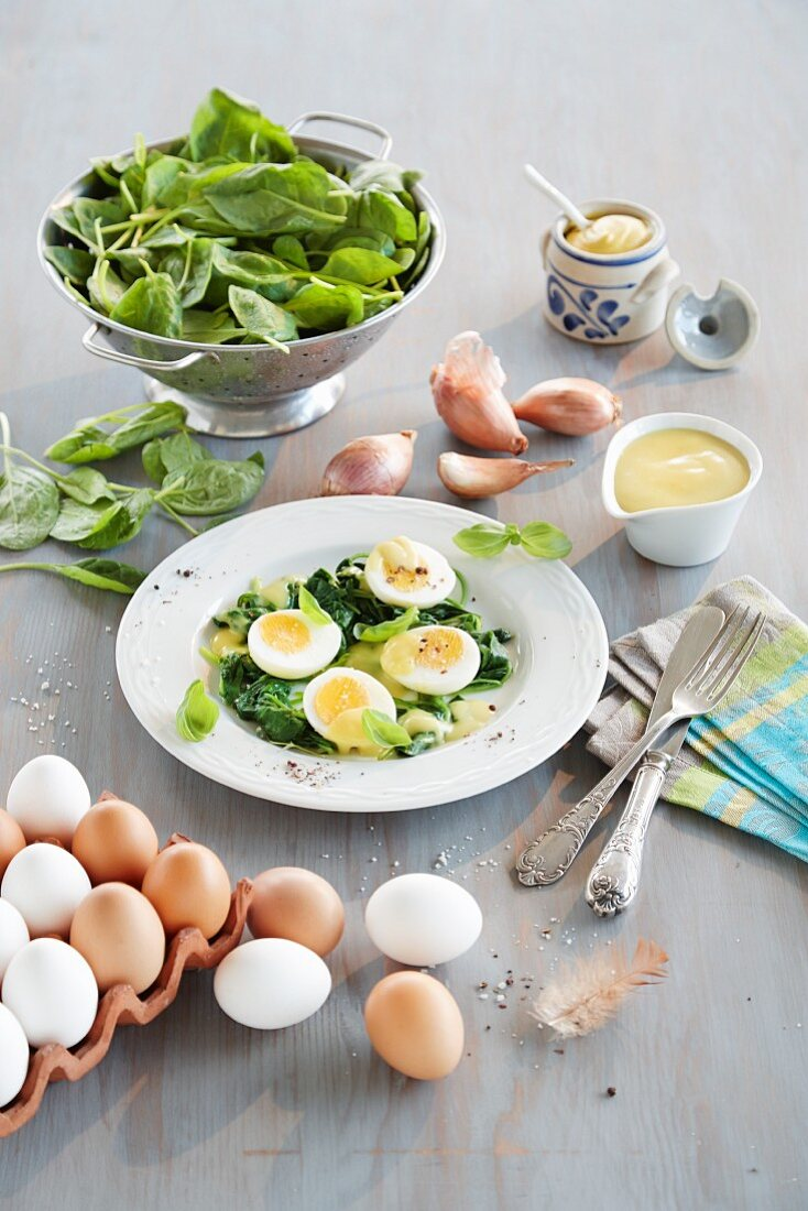 Eggs with mustard sauce and baby leaf spinach