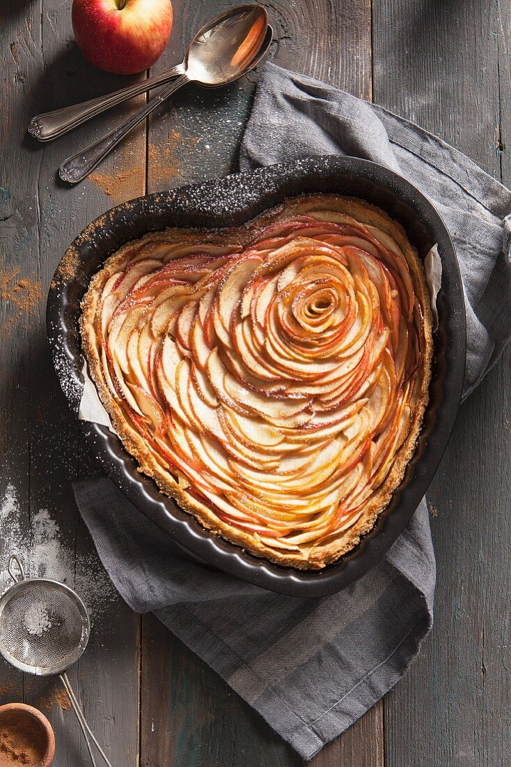 A heart-shaped apple tart with a dusting of icing sugar and cinnamon