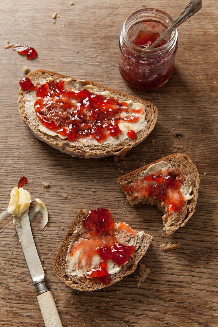 Two slices of fresh bread covered in butter and jam