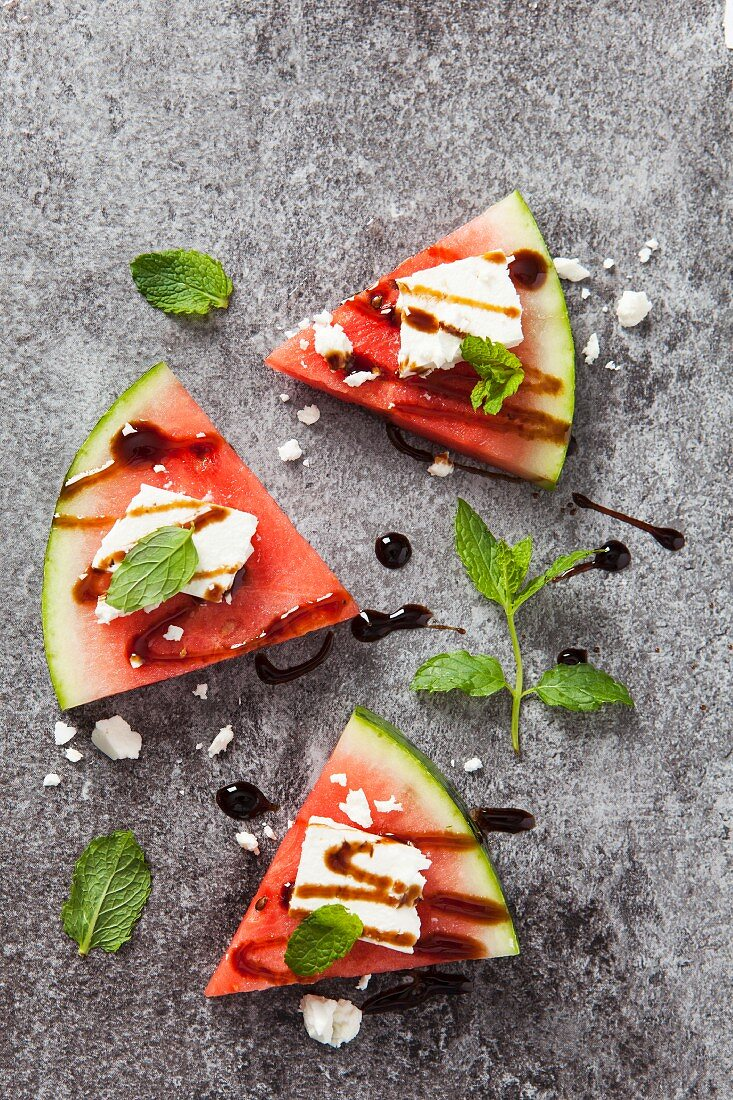 Three slices of fresh watermelon topped with feta cheese, balsamic syrup and fresh mint leaves
