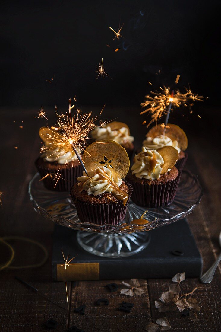 Apple and toffee cupcakes on a cake stand with apple crisps