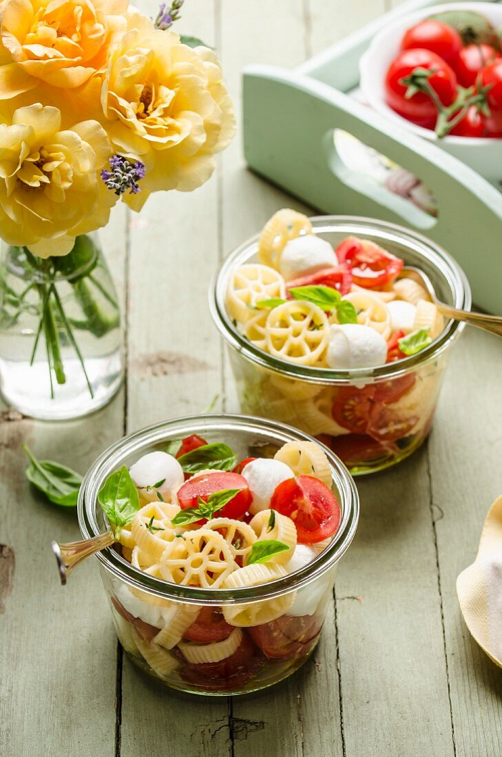 Pasta wheel salad with mozzarella cherry tomatoes and basil in the jar