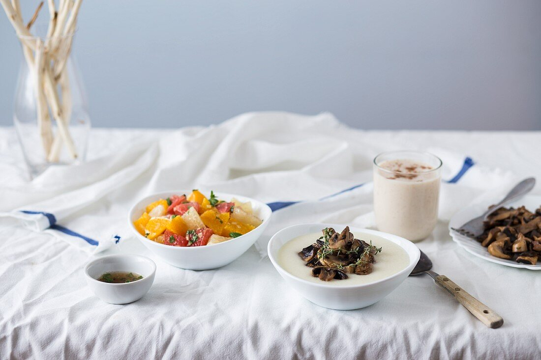 A set table with mushroom polenta; fruit salad and hot cinnamon drink