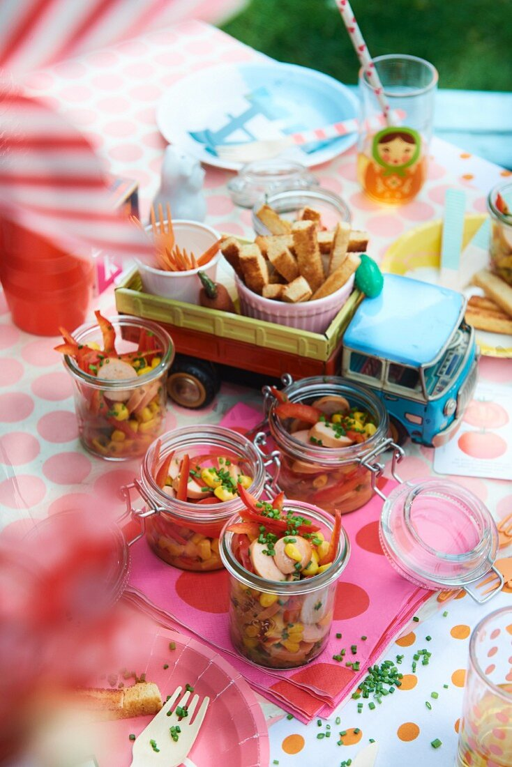 Red pepper and sweetcorn salad with sausages in glass jars and breadsticks for a children's party in the garden