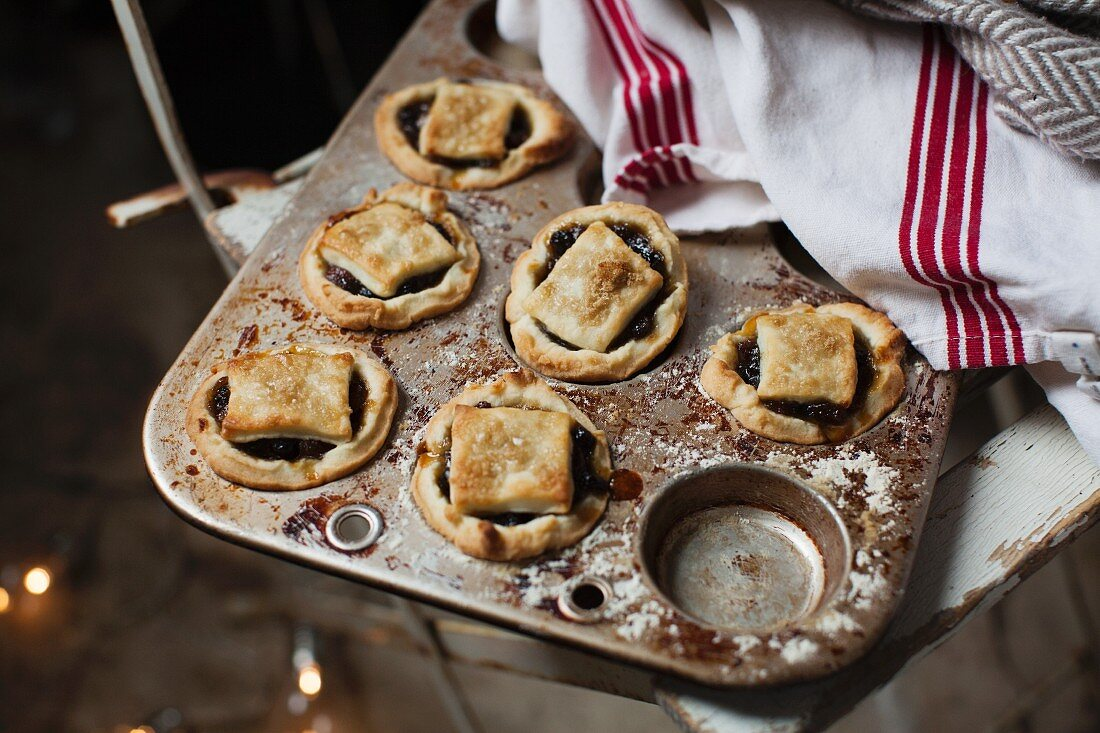 Six mince pies in a vintage baking tin with cream and red linen cloth on rustic white painted wooden chair