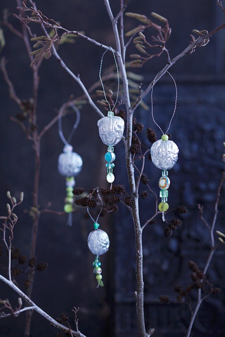 Silver walnuts with decorative beads on a tree for Christmas