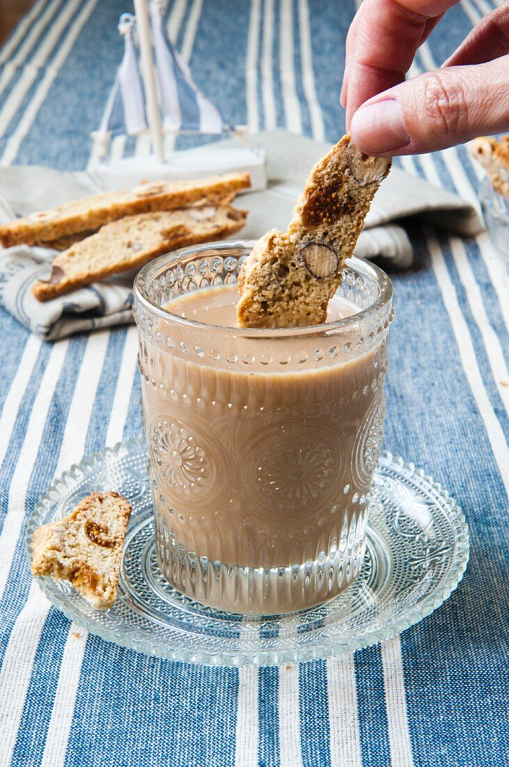 Biscotti with figs and nuts being dipped into coffee