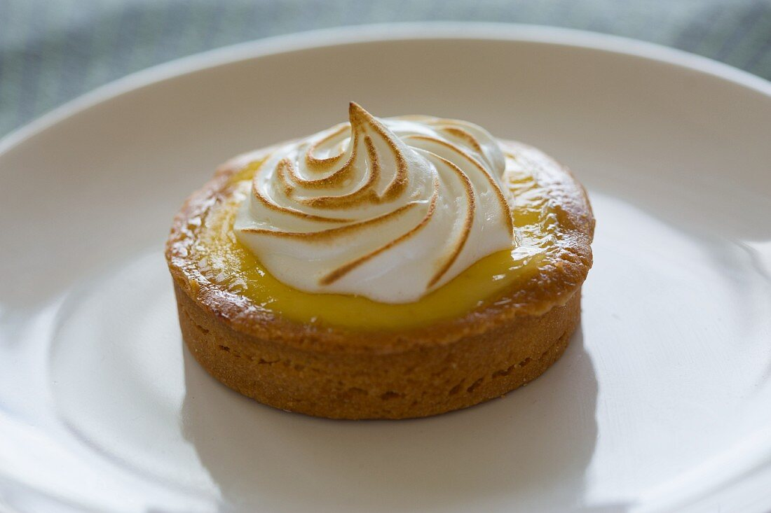 A small individual serving lemon tart and almond crust with meringue topping on a white plate