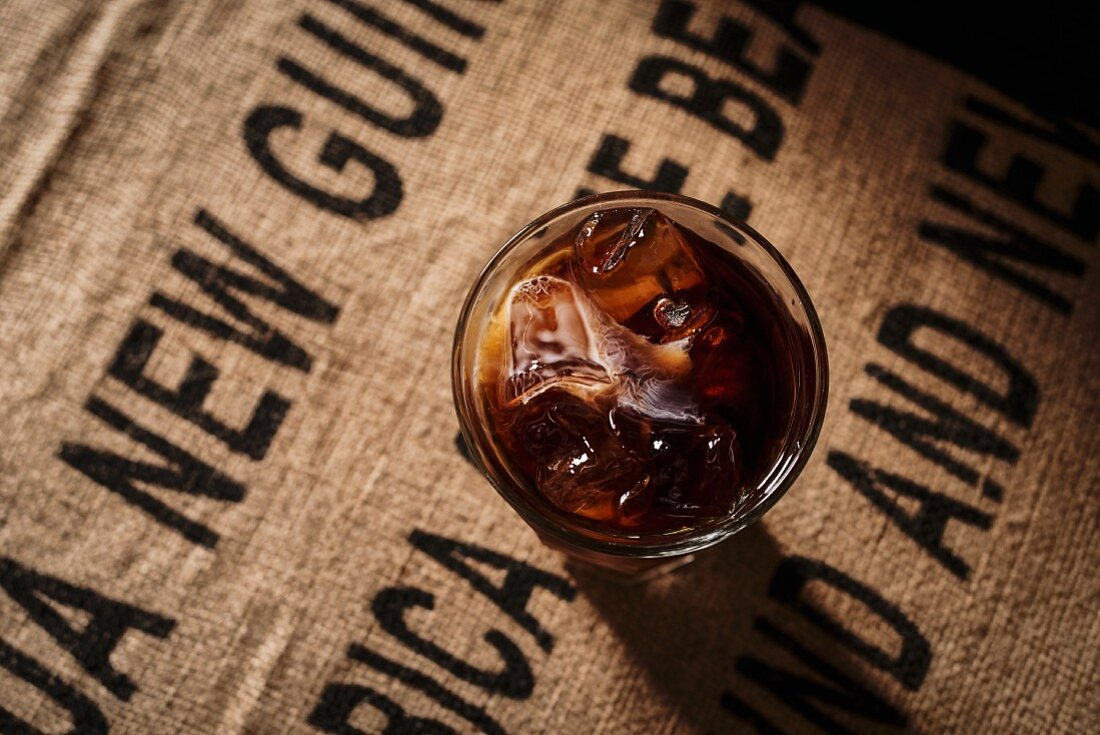 Iced coffee in a glass on a jute sack
