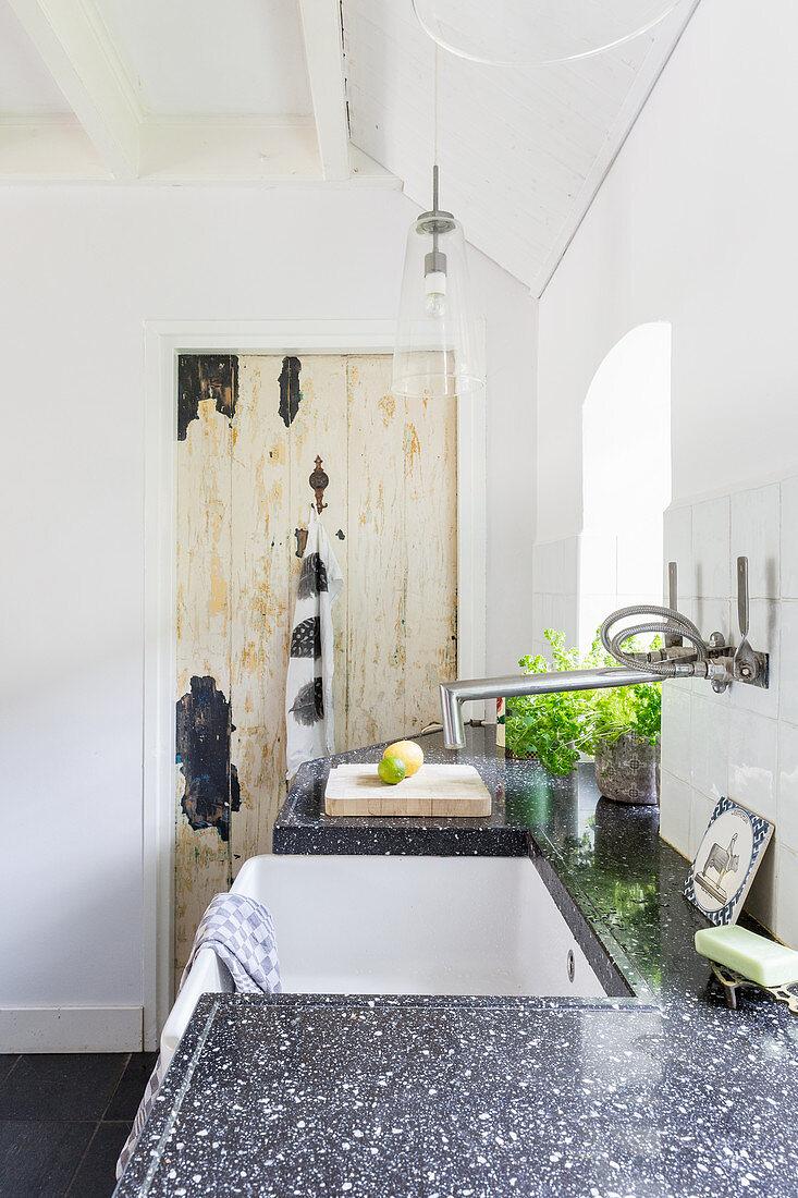 Black granite worksurface with ceramic farmhouse sink