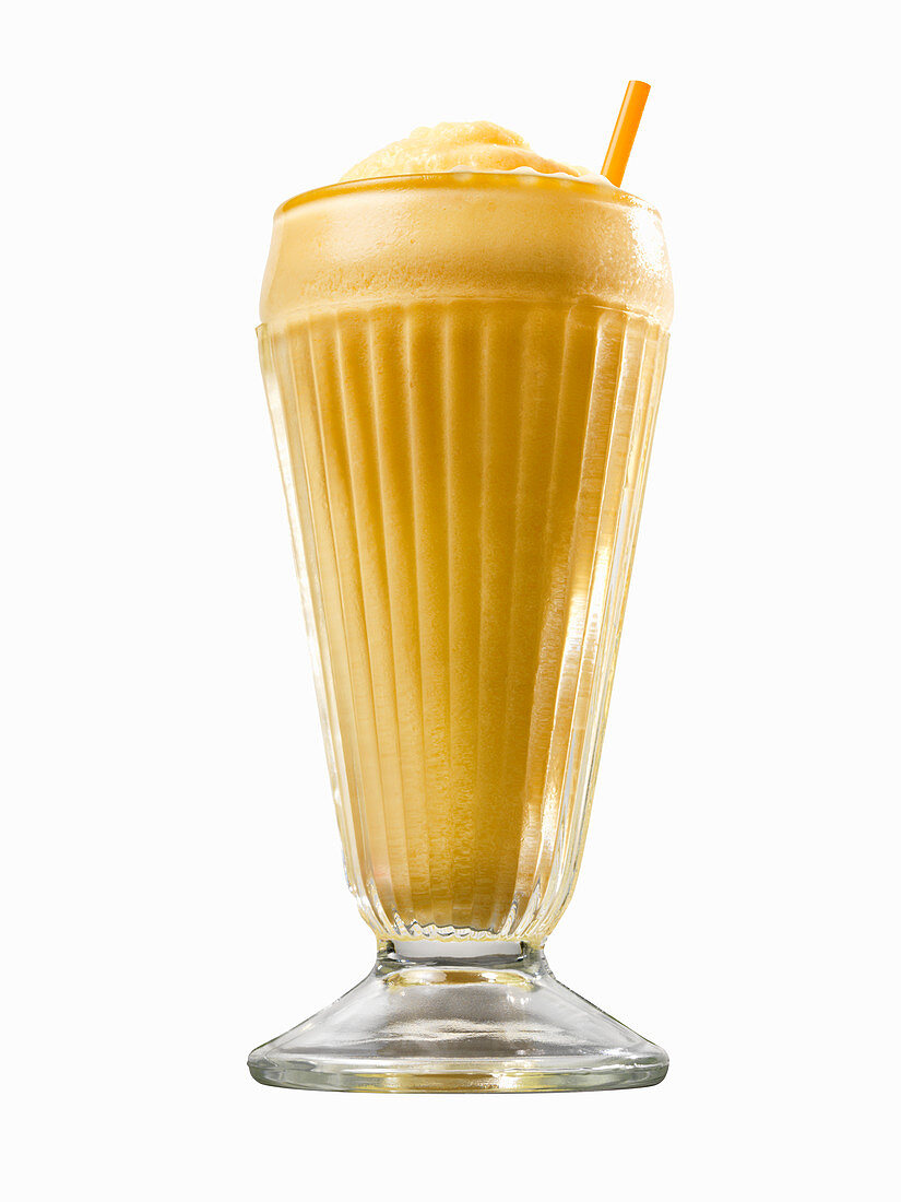An orange creamsicle in a glass with a straw