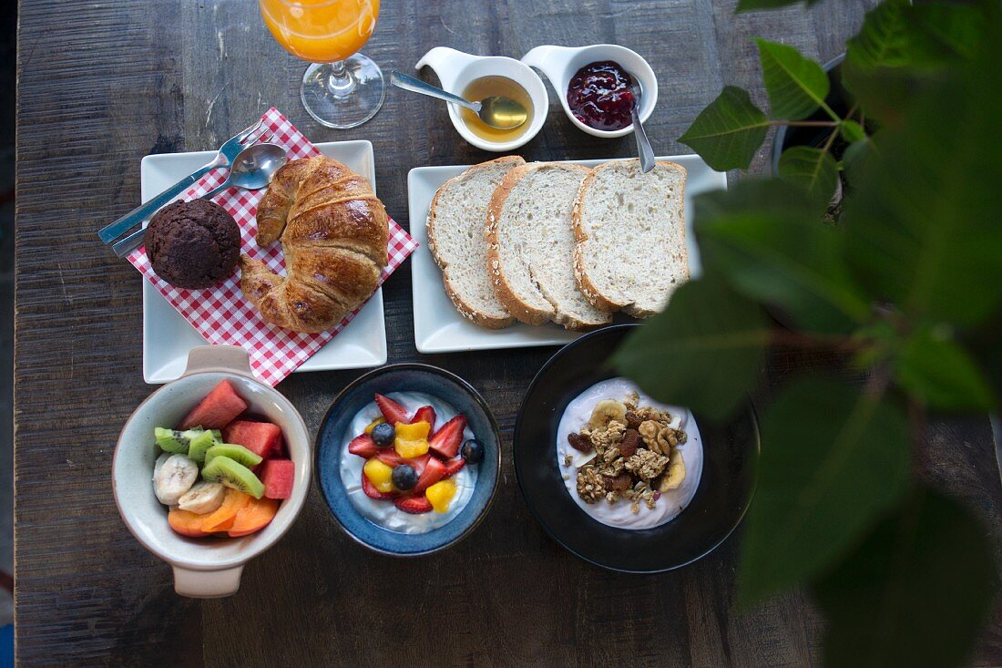 A breakfast with fruit salad, yoghurt and muesli, a croissant, white bread and jam