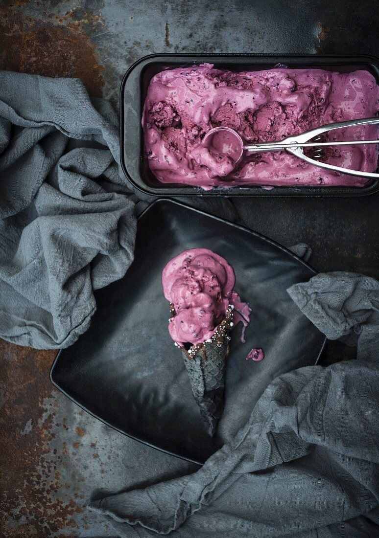 Vegan blackberry and peach ice cream in a black cone