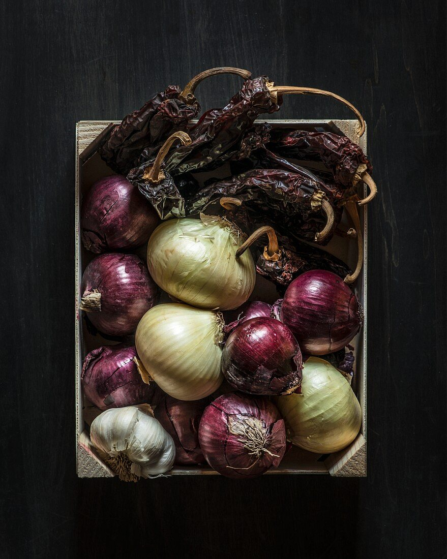 Raw onions, dried peppers and garlic in a wooden crate