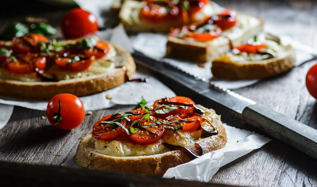 Slices of bread topped with cherry tomatoes, mozzarella and balsamic vinegar