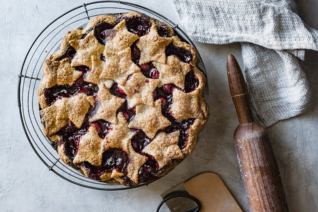 Gluten-free cherry pie with shortcrust pastry stars on a wire cooling rack