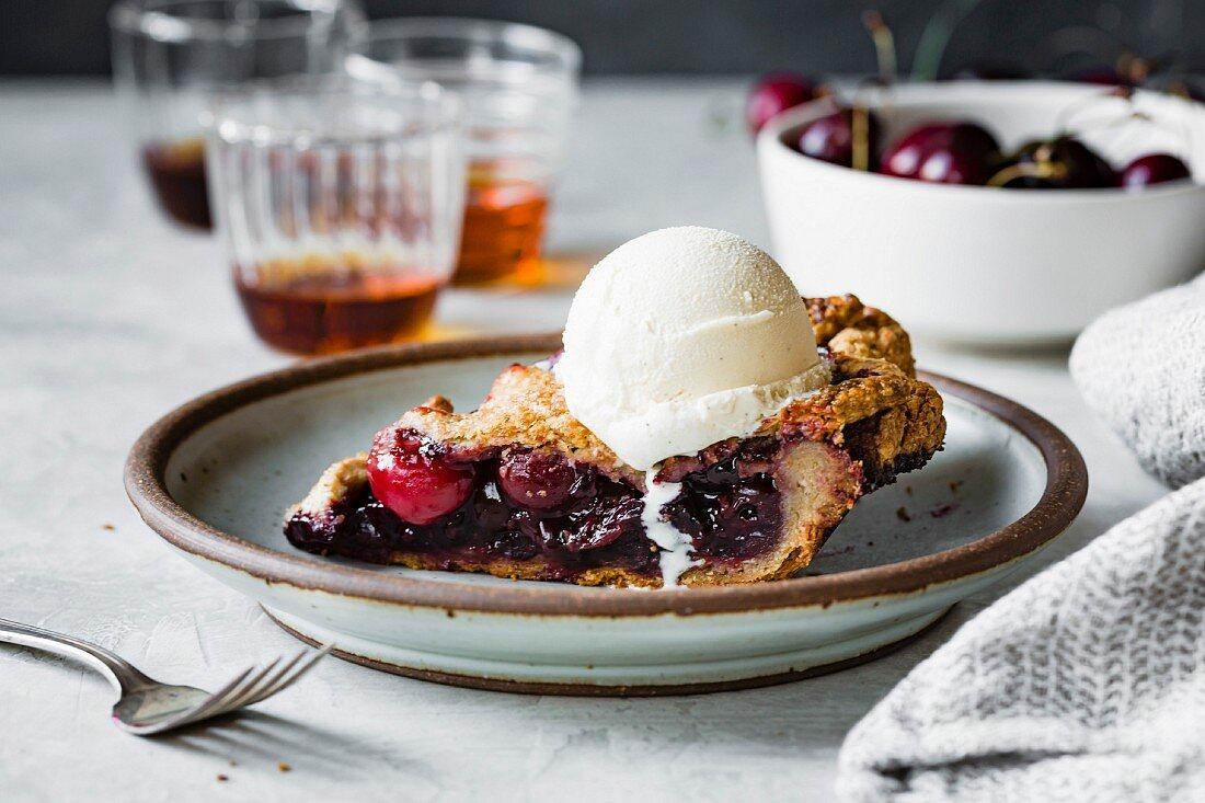 A slice of gluten-free cherry pie with vanilla ice cream on a plate