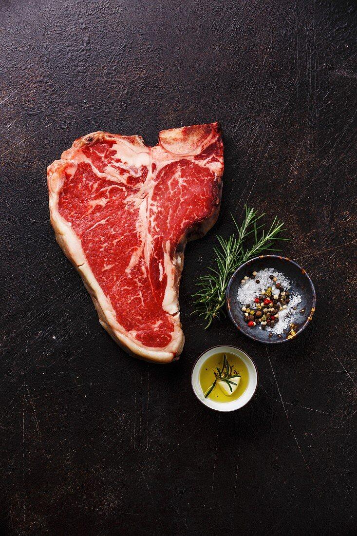 A raw dry-aged T-bone steak with seasoning on a black background