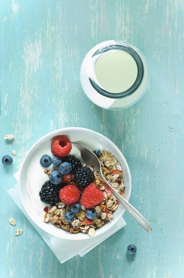 Yoghurt and muesli with berries in a bowl next to a glass bottle of yoghurt