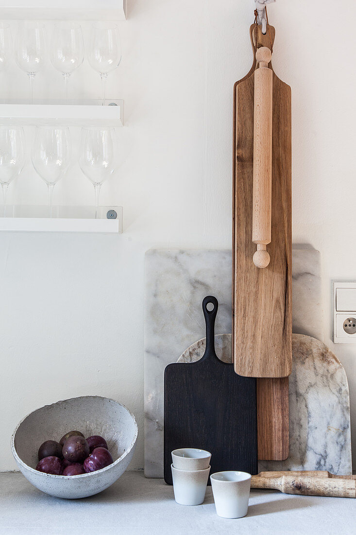 Various chopping boards and rolling pin on wall in kitchen