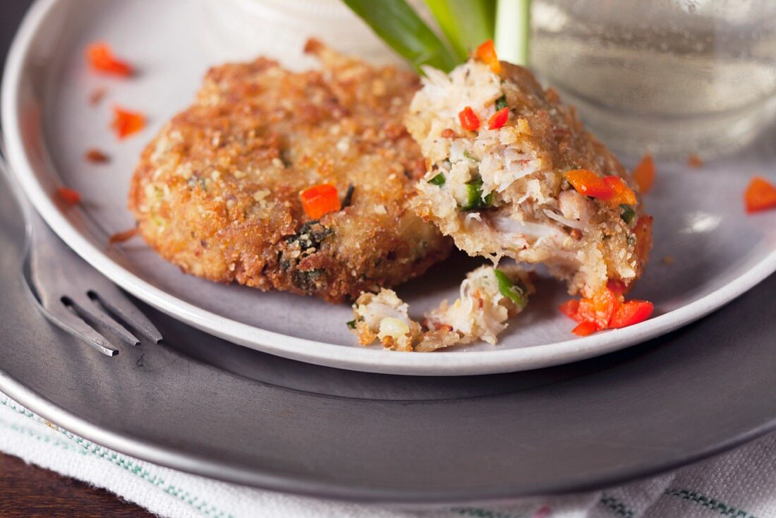 Partially eaten small crab cakes with red pepper