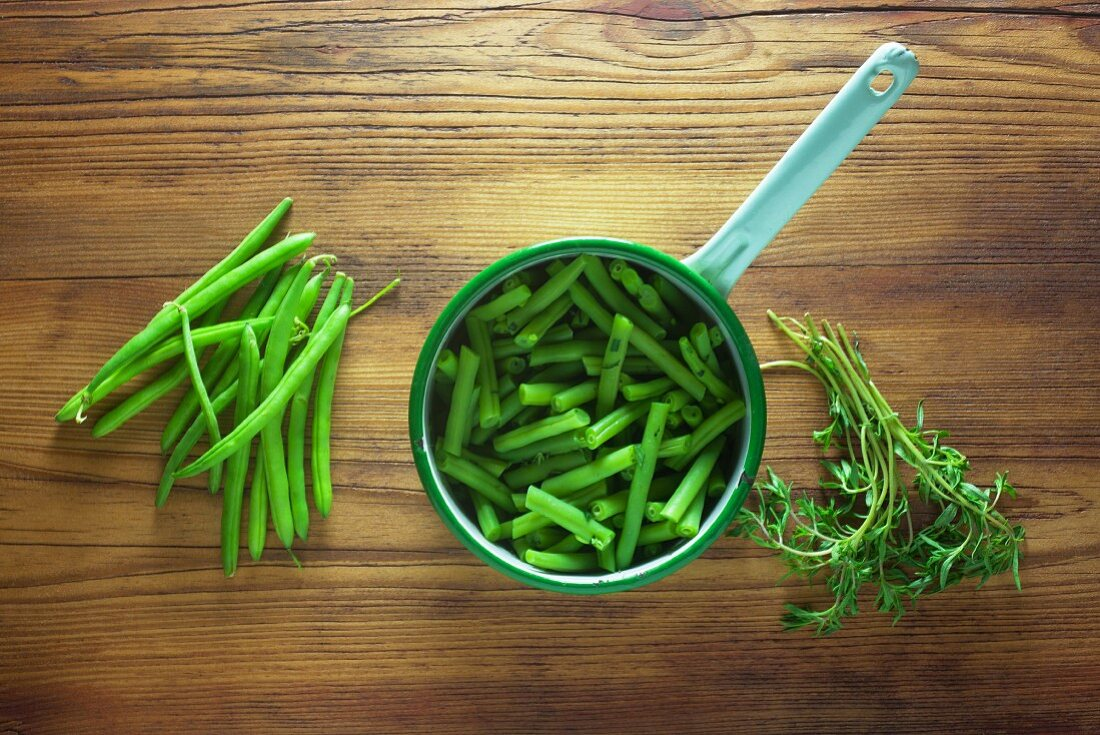 Green beans in a saucepan on a wooden table